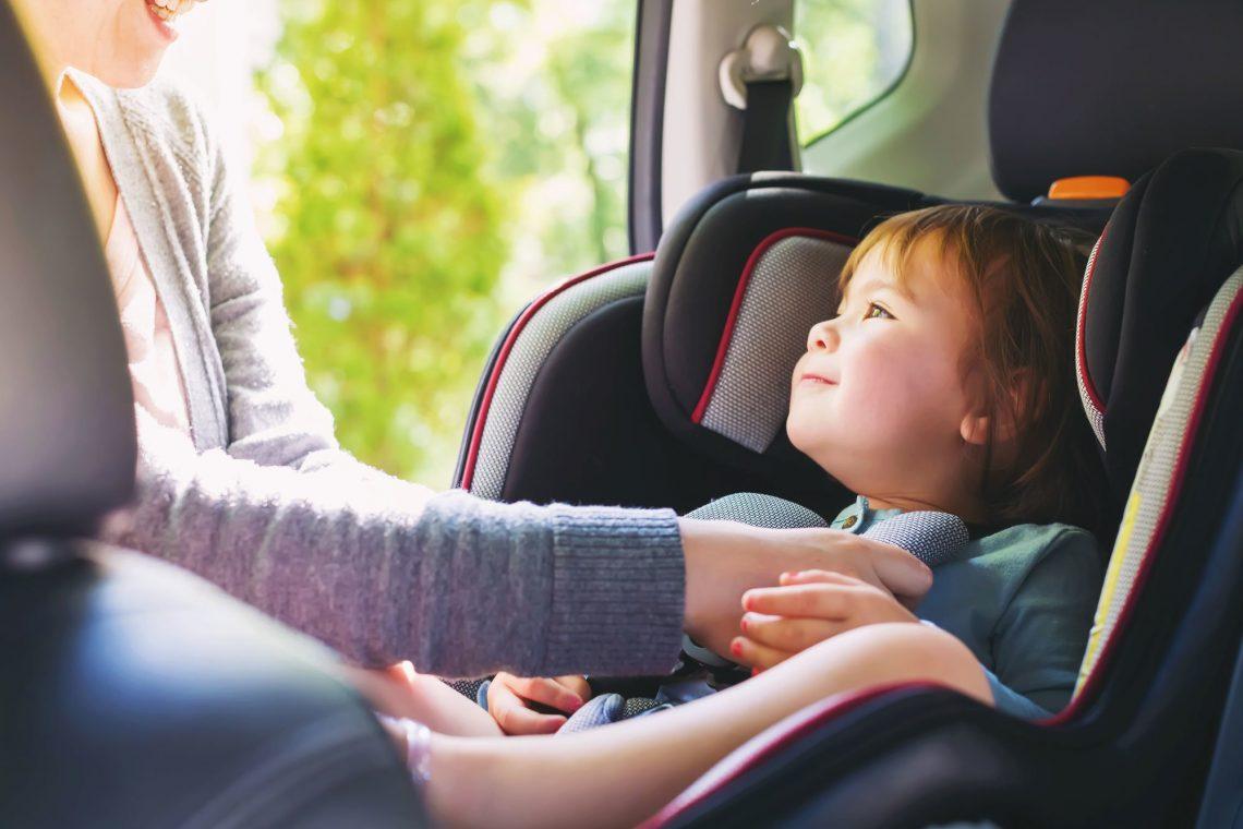Das Bild zeigt ein Kind im Auto, das im Kindersitz angeschnallt wird.