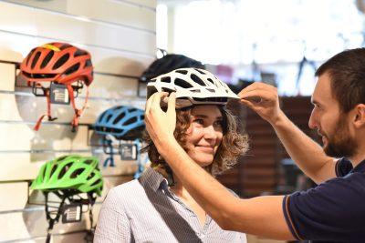 Das Bild zeigt eine Frau, die einen Fahrradhelm anprobiert.
