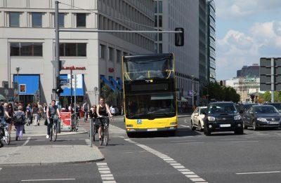 Innenstadt Berlin, ein Bus biegt an einer viel befahrenen Kreuzung ab, Radfahrer und Fußgängern sind auf der Straße
