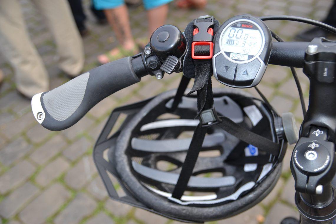 Das Bild zeigt einen Fahrradhelm, der am Lenker eines Pedelecs hängt.