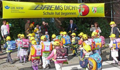 Das Bild zeigt Schulanfänger unter dem Spannband Brems Dich! Schule hat begonnen.