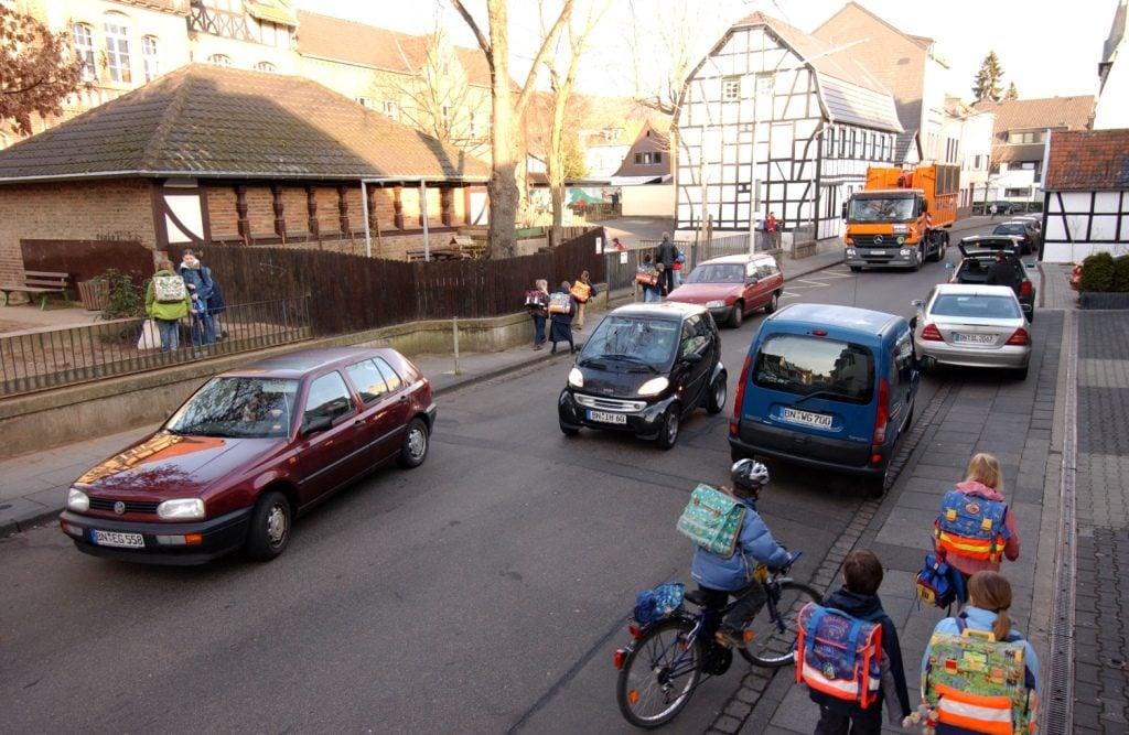 Das Bild zeigt Autos und Schulkinder vor einer Schule.