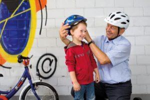 Das Bild zeigt einen Großvater mit Fahrradhelm, der seinem Enkel einen Helm aufsetzt.