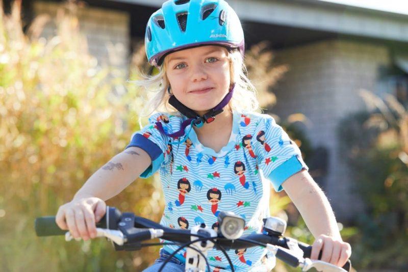 Das Bild zeigt ein Mädchen mit Helm auf dem Fahrrad.