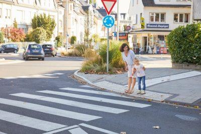 Das Bild zeigt eine Frau, die mit ihrer Tochter am Zebrastreifen wartet.
