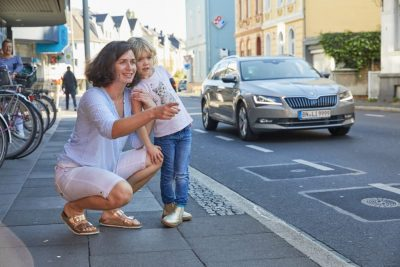 Das Bild zeigt eine Frau, die sich mit ihrer Tochter auf dem Gehweg befindet und vorbeifahrende Autos beobachtet.