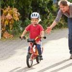 Das Bild zeigt eine Frau, die ein Kind auf dem Fahrrad anschiebt.