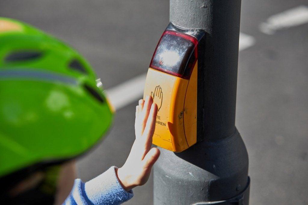 Das Bild zeigt eine Kinderhand, die an der Fußgängerampel den gelben Knopf drückt.
